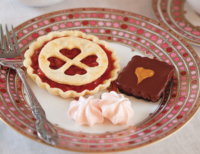 These three Valentine's Day sweets are Cherry Tartlets (left), Strawberry Meringue Kisses (center), and Chocolate–Peanut Butter Tartlets (right).
