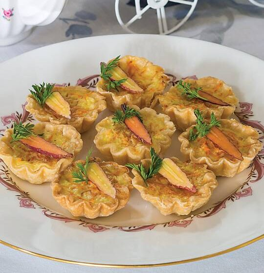 Parmesan and prosciutto quiches get an unexpected flavor boost as well as a texture contrast from two types of carrot—coarsely grated bits baked into the egg filling and raw tiny ones perched on top as a garnish.